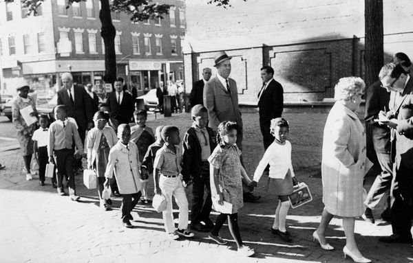 Mary Lynch, an assistant principal at a school in Boston's Roxbury community, leads first graders to a school in the city's N