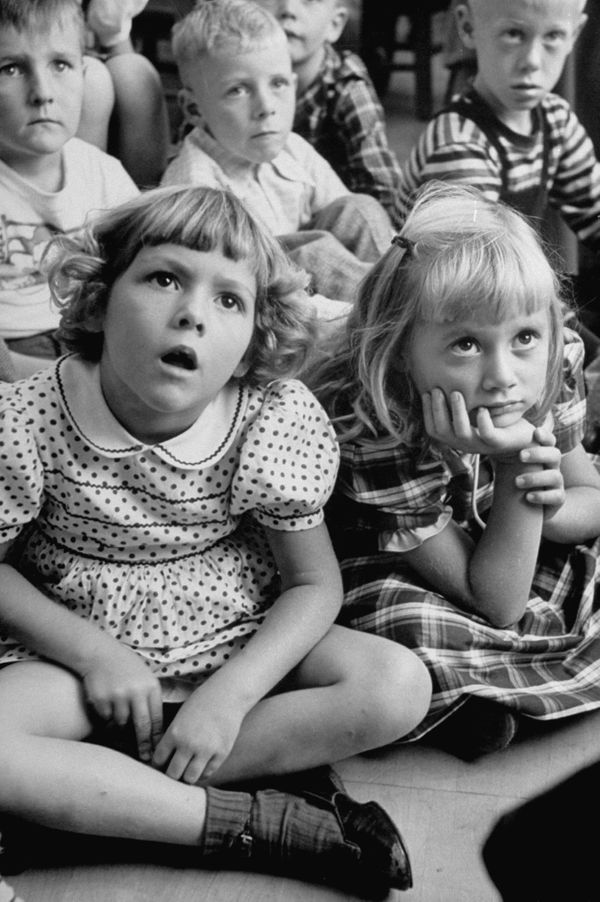 Wide-eyed children listening to fairy-tales on their first school day in 1949.