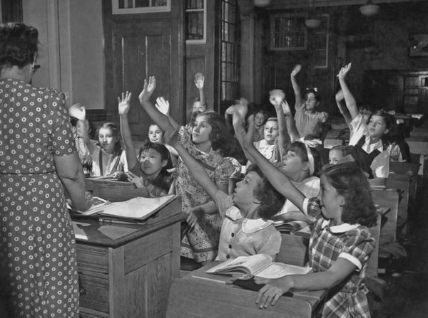 Students eagerly vie to be called on at a New York school, circa 1950.