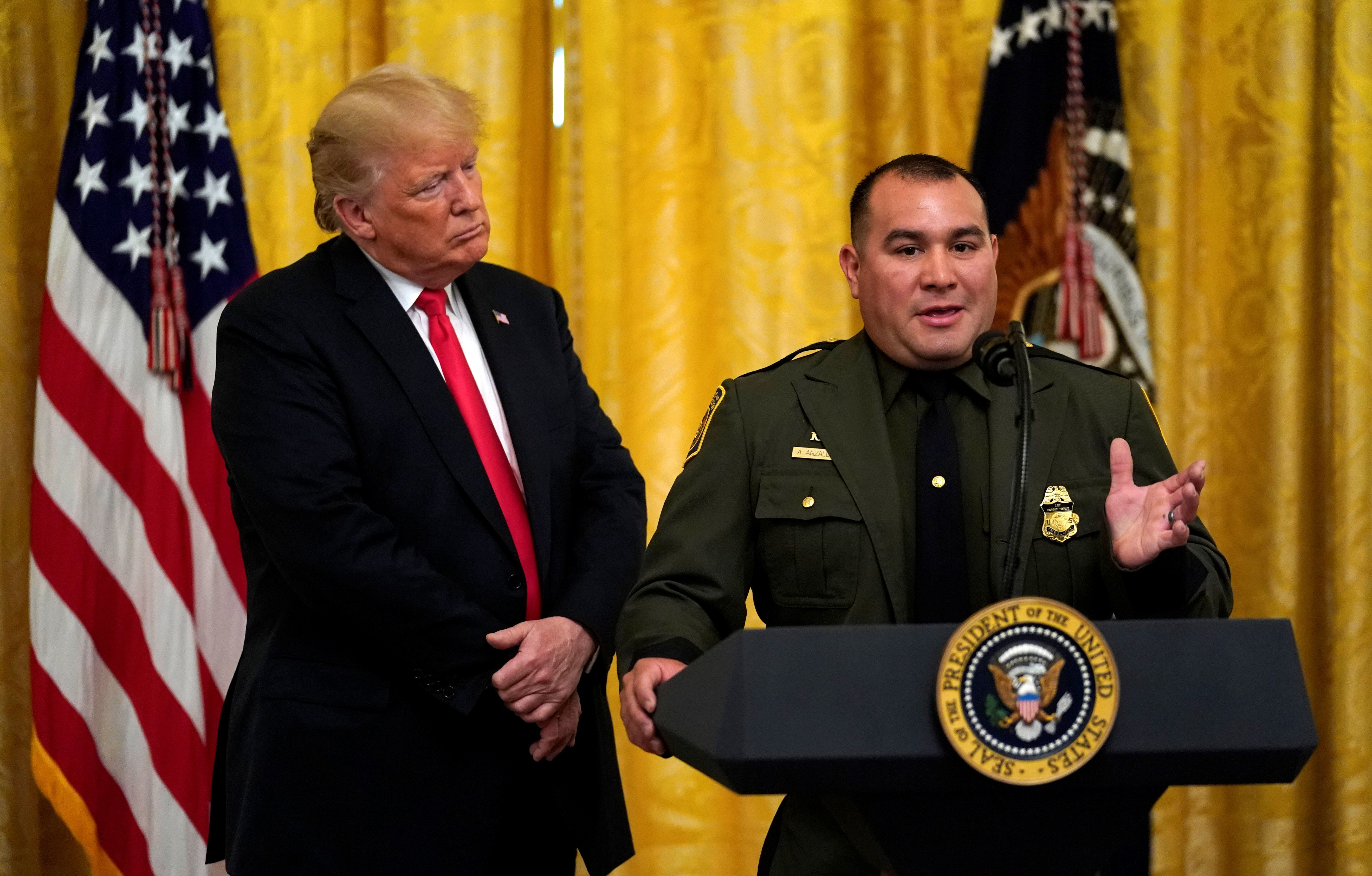 U.S. President Donald Trump listens to Border Patrol agent Adrian Anzaldua speak  during a Salute to the Heroes event at the White House in Washington, U.S., August 20, 2018.  REUTERS/Kevin Lamarque