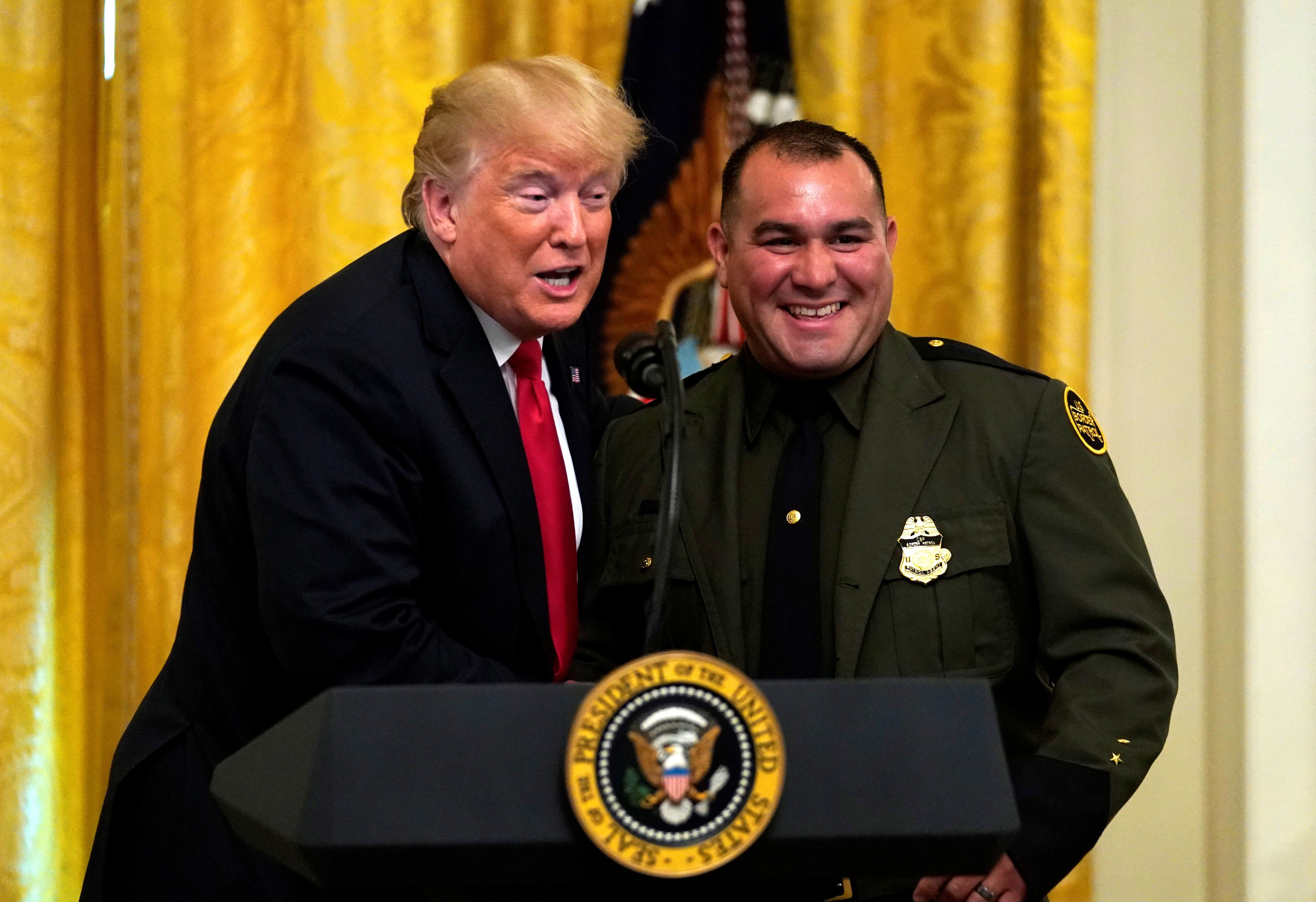 U.S. President Donald Trump brings up Border Patrol agent Adrian Anzaldua to speak  during a Salute to the Heroes event at the White House in Washington, U.S., August 20, 2018.  REUTERS/Kevin Lamarque