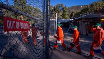 Prisoners at Oak Glen Conservation Camp leave the minimum security prison for work deployment under the authority of Cal Fire, during which time they are called and treated as firefighters rather than inmates until they return to camp, on September 28, 2017 near Yucaipa, California. / AFP PHOTO / DAVID MCNEW        (Photo credit should read DAVID MCNEW/AFP/Getty Images)