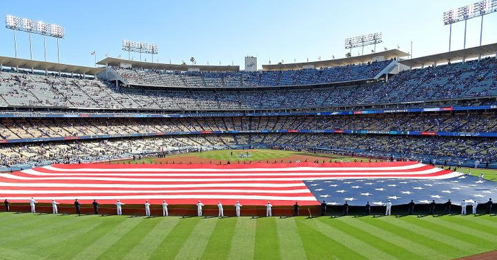 Armed forces service members hold an American flag in the outfield during the National Anthem before the game between the Los