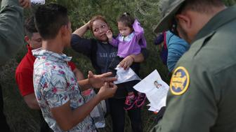 MCALLEN, TX - JUNE 12:  U.S. Border Patrol agents ask a group of Central American asylum seekers to remove hair bands and weddding rings before taking them into custody on June 12, 2018 near McAllen, Texas. The immigrant families were then sent to a U.S. Customs and Border Protection (CBP) processing center for possible separation. U.S. border authorities are executing the Trump administration's 'zero tolerance' policy towards undocumented immigrants. U.S. Attorney General Jeff Sessions also said that domestic and gang violence in immigrants' country of origin would no longer qualify them for political asylum status.  (Photo by John Moore/Getty Images)