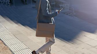 Businessman walking on staircase with bags, outside at sunrise