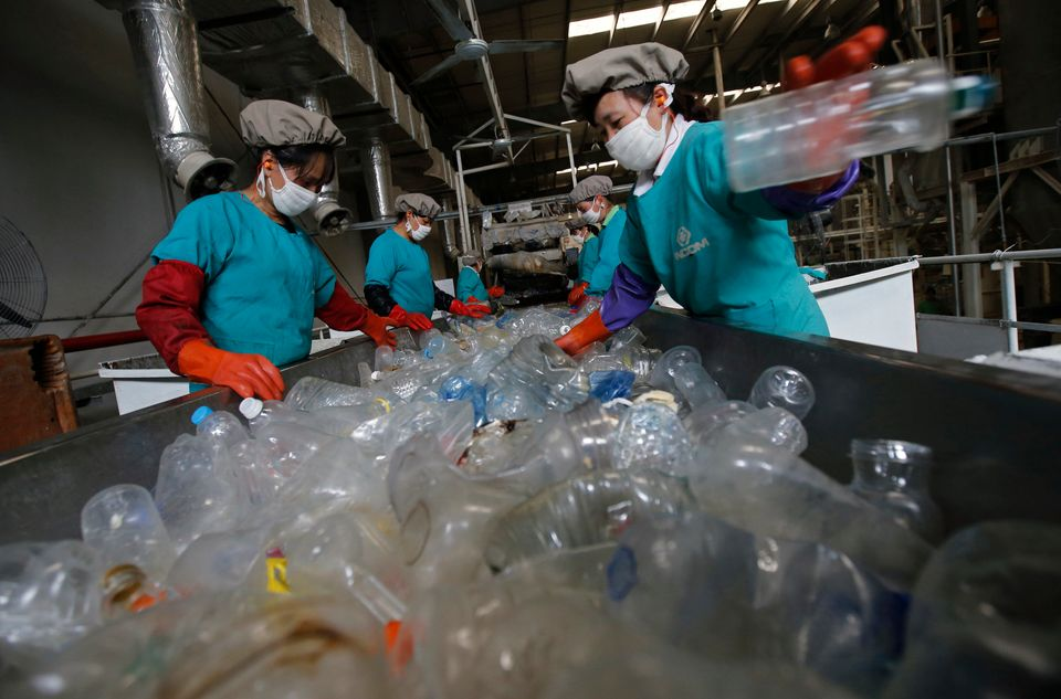 Workers sort through plastic bottles at a recycling facility in