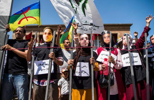 Des manifestants portent des masques montrant les visages des activistes du Hirak condamnés à...