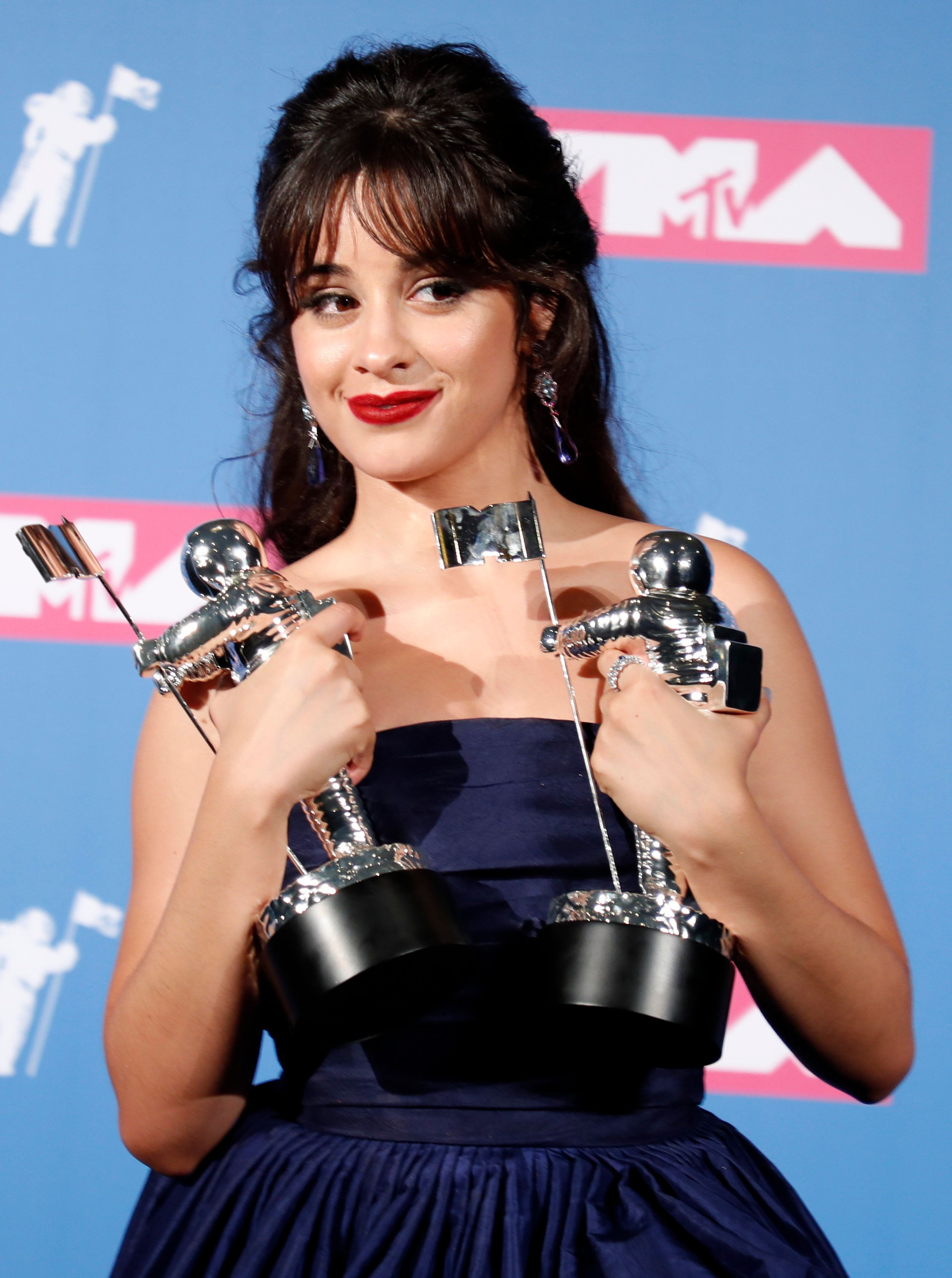 """2018 MTV Video Music Awards - Photo Room - Radio City Music Hall, New York, U.S., August 20, 2018. - Camila Cabello poses backstage with her awards for Artist of the Year and Video of the Year for """"Havana."""" REUTERS/Carlo Allegri"""