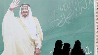 Women walk past a poster of Saudi Arabia's King Salman bin Abdulaziz Al Saud during Janadriyah Cultural Festival on the outskirts of Riyadh, Saudi Arabia February 12, 2018. Picture taken February 12, 2018. REUTERS/Faisal Al Nasser
