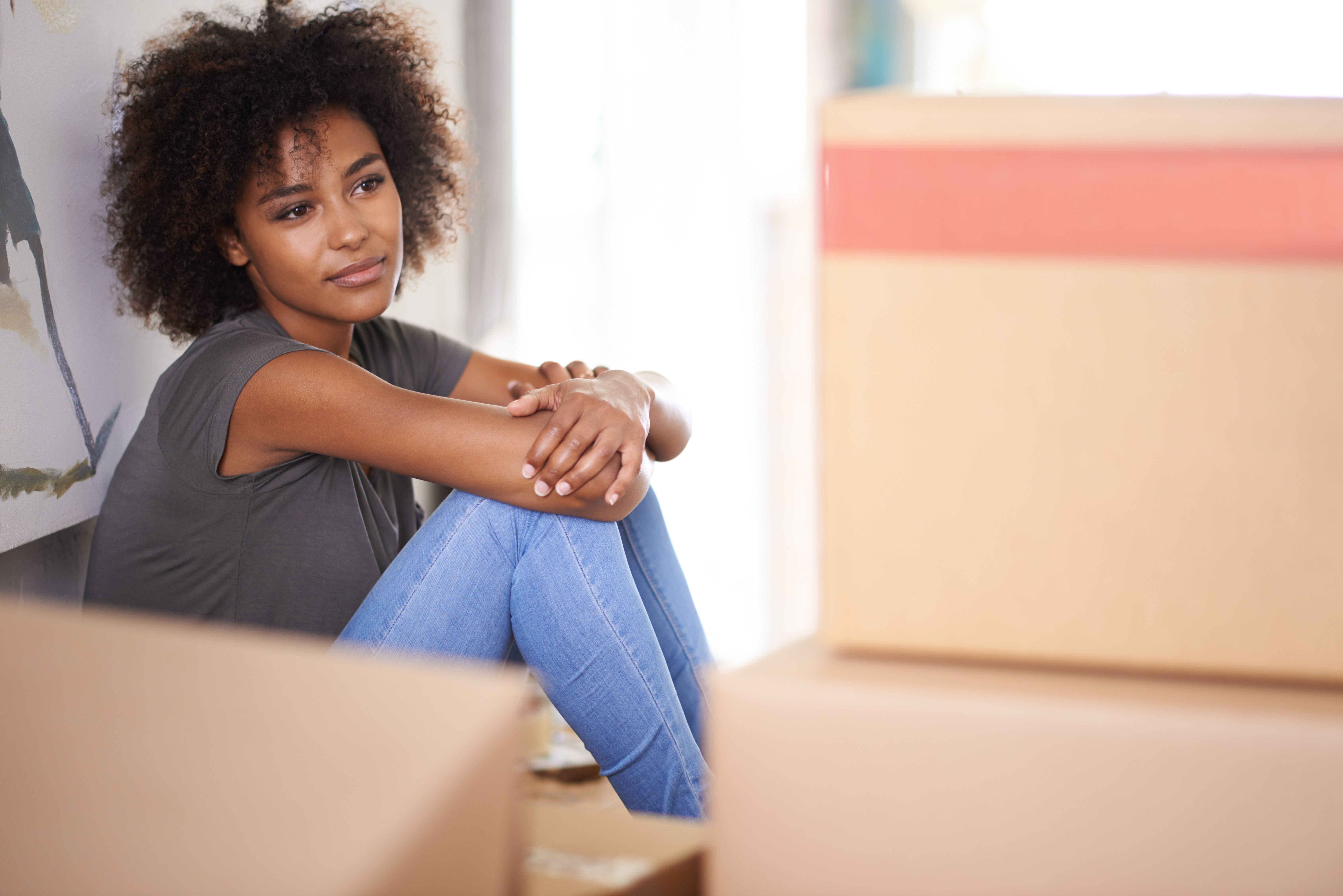 Shot of an attractive young woman feeling nostalgic while sitting amongst packed boxes