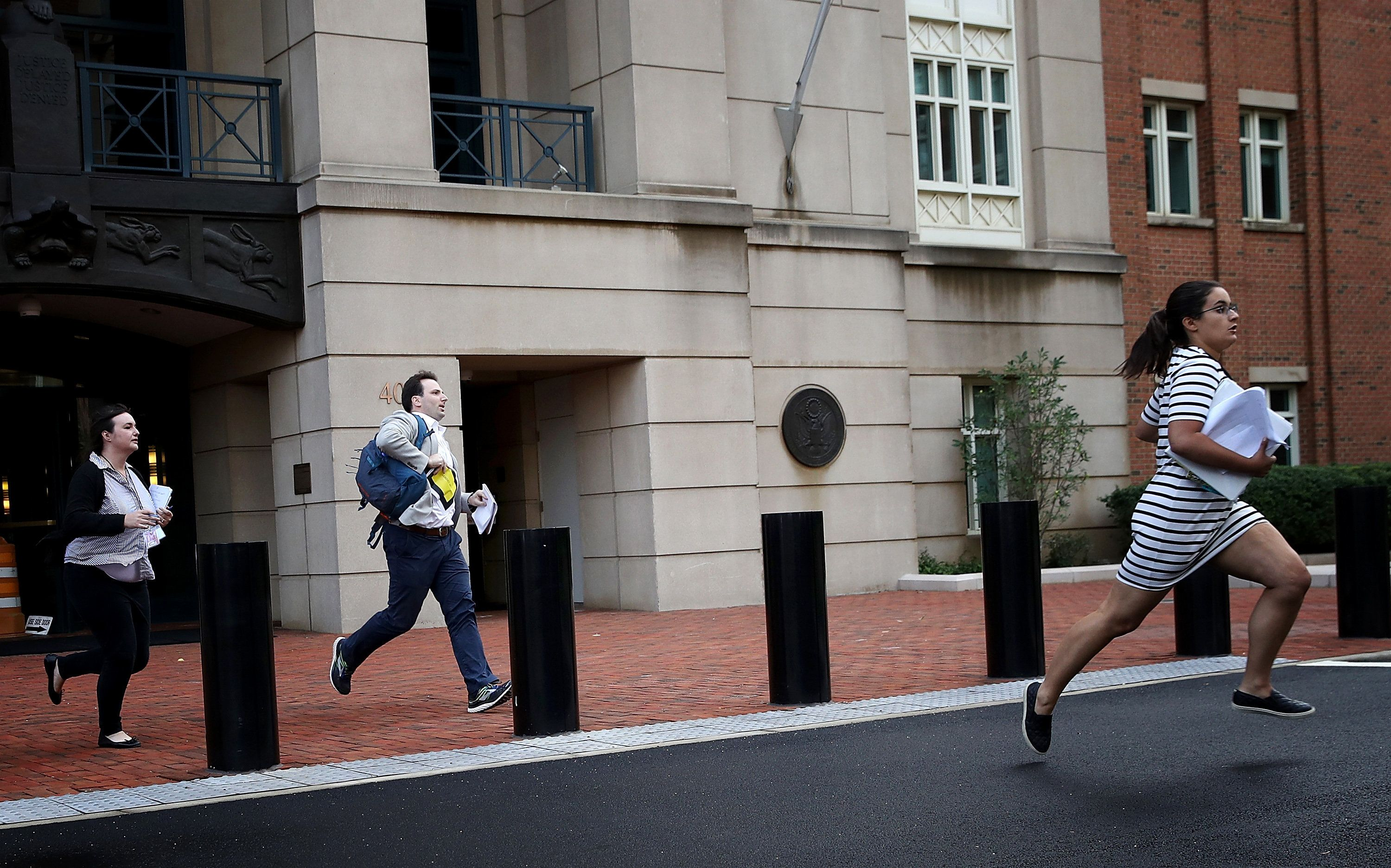 ALEXANDRIA, VA - AUGUST 21:  Reporters run from the Albert V. Bryan United States Courthouse with news of the verdict in the case of former Trump campaign chairman Paul Manafort August 21, 2018 in Alexandria, Virginia. Manafort was found guilty on 8 out of 18 counts of bank and tax fraud as part of special counsel Robert Mueller's investigation into Russian interference in the 2016 presidential election. (Photo by Win McNamee/Getty Images)