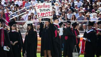 STANFORD, CA - JUNE 12:  Graduating student, Andrea Lorei, who help organize campus demonstrations holds a sign in protest during the 'Wacky Walk' before the 125th Stanford University commencement ceremony on June 12, 2016 in Stanford, California. The university holds its commencement ceremony amid an on-campus rape case and its controversial sentencing. (Photo by Ramin Talaie/Getty Images)
