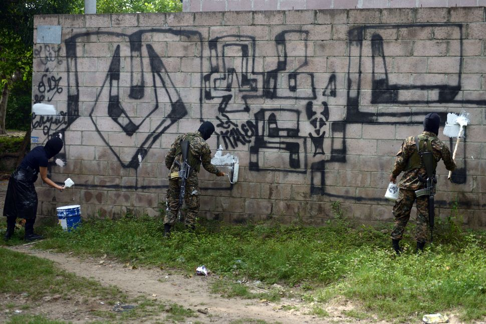 Police officers and soldiers paint over graffiti associated with the Mara Salvatrucha gang, or MS-13, in Quezaltepeque,