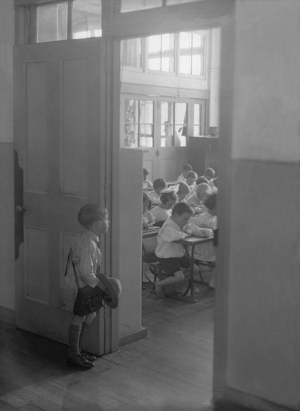 A young Australian boy stares into a classroom already full of students, circa 1930.