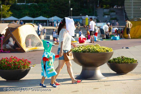 지난 11일 서울에서 어른과 아이가 열기를 피하기 위해 얼굴을 가린 채 걷고