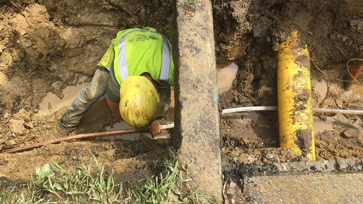 After digging out the road and lawn, a worker ducks under the curb while connecting a copper pipe on private property with a