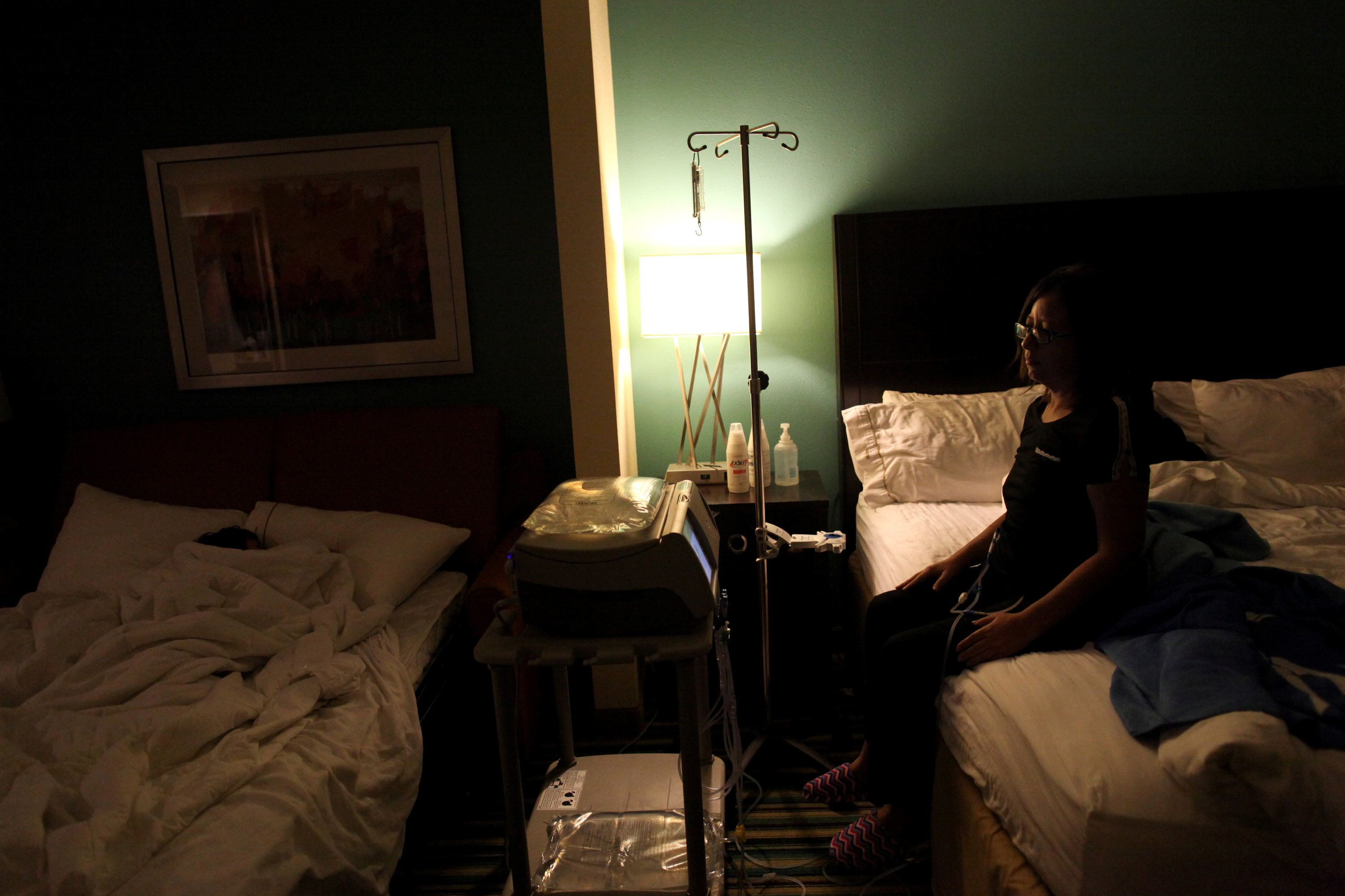 """Puerto Rican Waleska Rivera, 42, looks at her sleeping son Ethan Alejandro Oyola, 9, as she undergoes her dialysis treatment in a hotel room, where she lives with her family, in Orlando, Florida, U.S., December 7, 2017. Waleska left Puerto Rico with her family when Hurricane Maria struck the island in late September. The hotel provides a temporary housing for displaced Puerto Ricans. REUTERS/Alvin Baez      SEARCH """"PUERTO RICO FLORIDA"""" FOR THIS STORY. SEARCH """"WIDER IMAGE"""" FOR ALL STORIES."""