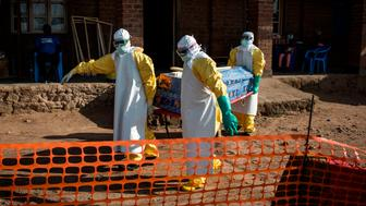 Medical workers carry the corpse of a unconfirmed Ebola case in an Ebola Treatment Centre run by The Alliance for International Medical Action (ALIMA) on August 13, 2018, in Beni. (Photo by John WESSELS / AFP)        (Photo credit should read JOHN WESSELS/AFP/Getty Images)