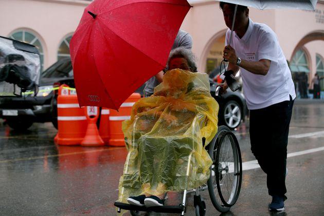 태풍 솔릭의 영향으로 많은 비가 내리는 24일 강원도 속초 한화리조트에서 21차 이산가족 상봉행사 2회차 상봉 대상자들이 상봉장으로 가기위해 버스로 향하고