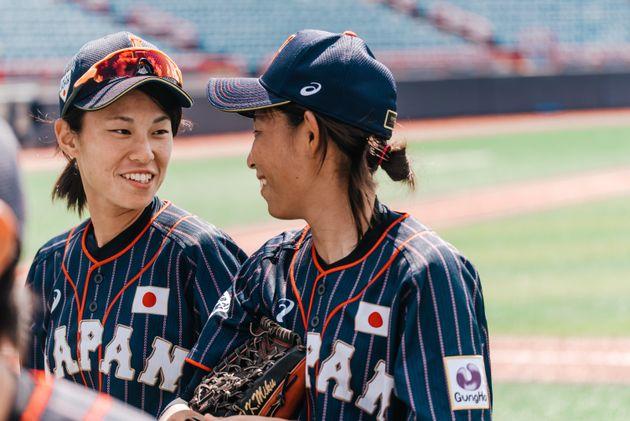 Rina Taniyama (left) and Miku Kitayama (right) talk during theWomen's Baseball World Cup as Japan...