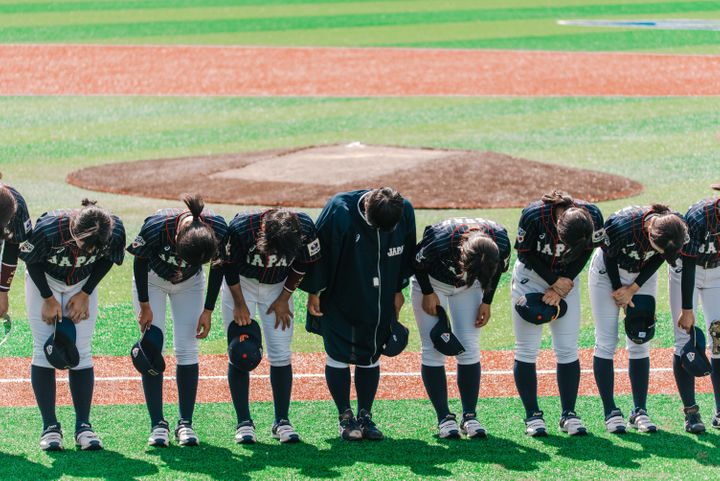 Team Japan bows during a game against Hong Kong at the Women's Baseball World Cup.