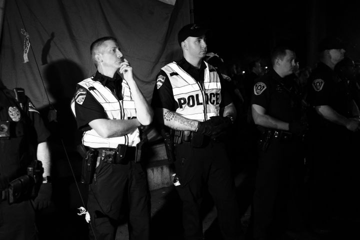 "Officer Cole Daniels (center) at the Aug. 20 ""Silent Sam"" protest with a Three Percenters tattoo visible on his right arm."