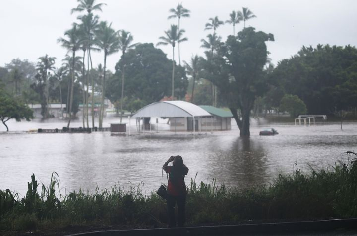 Awoman takes photos of floodwaters from Hurricane Lane rainfall on the Big Island on Aug. 23, 2018, in Hilo, Hawaii.