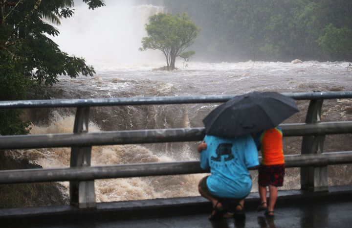 People gather on a bridge to watch the Wailuku River flood waters on the Big Island in Hilo.