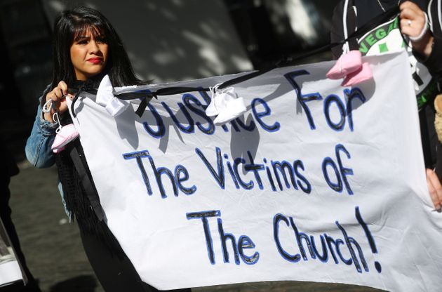 Protesters hold banners during a demonstration against clerical sex abuse, in Dublin, Ireland August...
