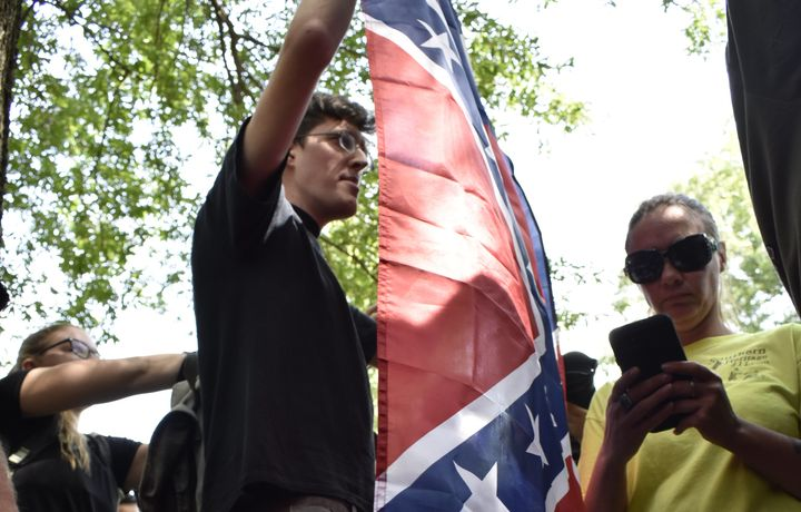 A man identified as Paul Kin holds a Confederate flag during a rally at the University of North Carolina, Chap