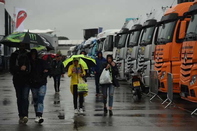 People shelter under umbrellas and raincoats as the start of the MotoGP race is delayed due to rain during...