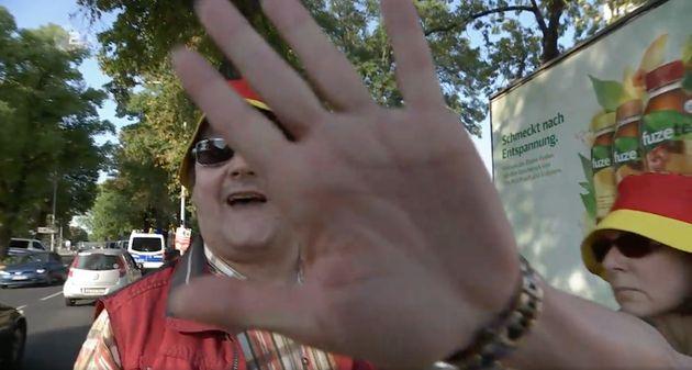 Eine Frau schlägt bei einer Pegida-Demonstration gegen die Kamera eines