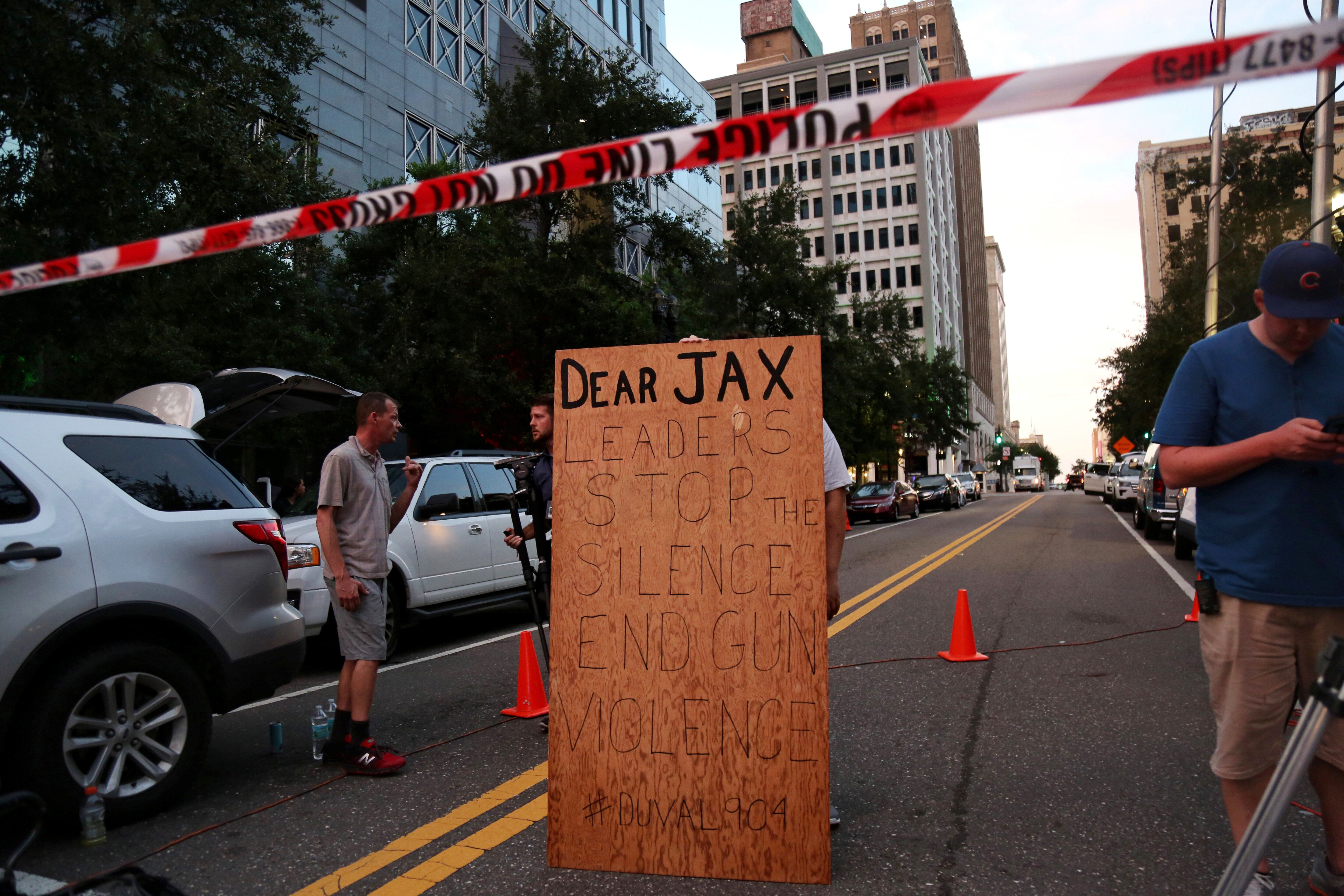 A man holds a sign in support of gun control outside of The Jacksonville Landing after a shooting in Jacksonville, Florida August 26, 2018.  REUTERS/Joey Roulette