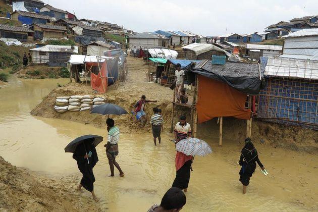 방글라데시에 위치한 로힝야 난민 캠프 사람들이 우기에 침수된 거리를 걸어가고