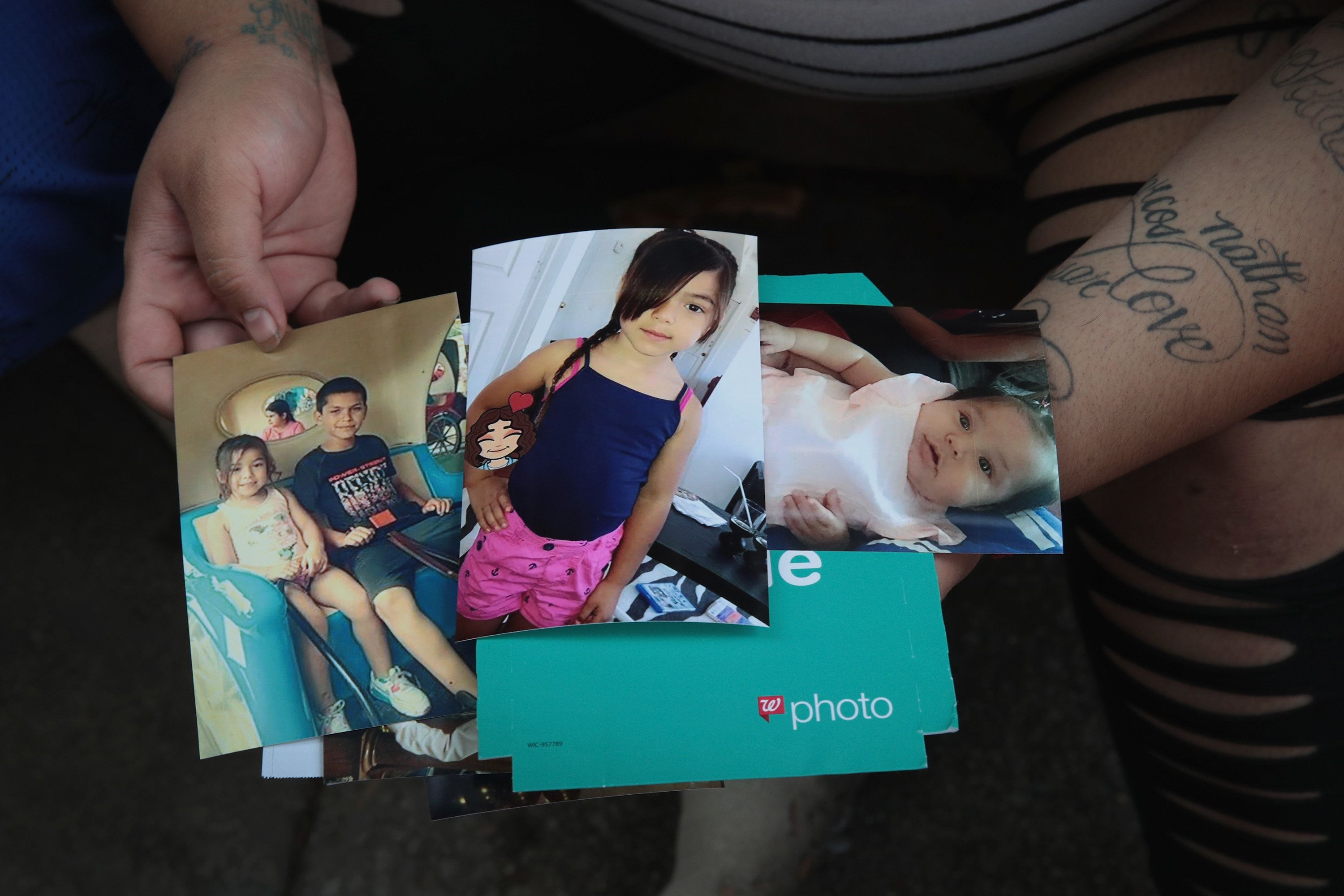 Amber Ayala looks through pictures of her brothers and sisters who were killed in an early-morning fire in the Little Village