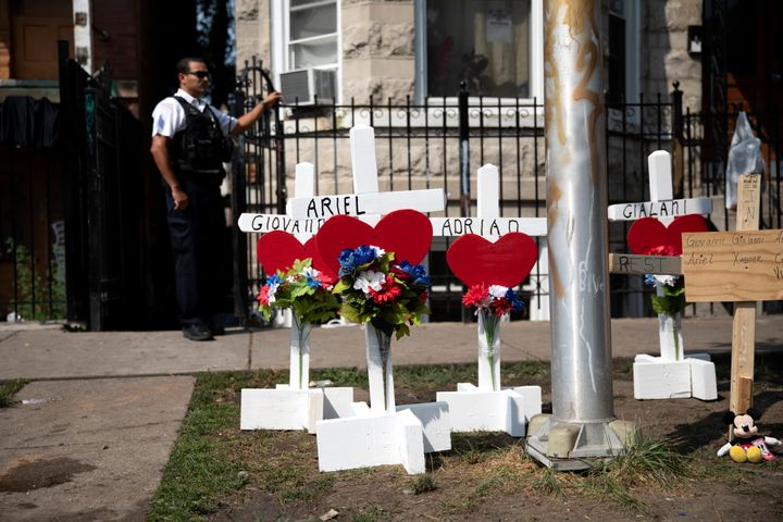 Wood crosses hold victims' names at the scene of a fire that killed at least eight people, including six children, on Sunday,