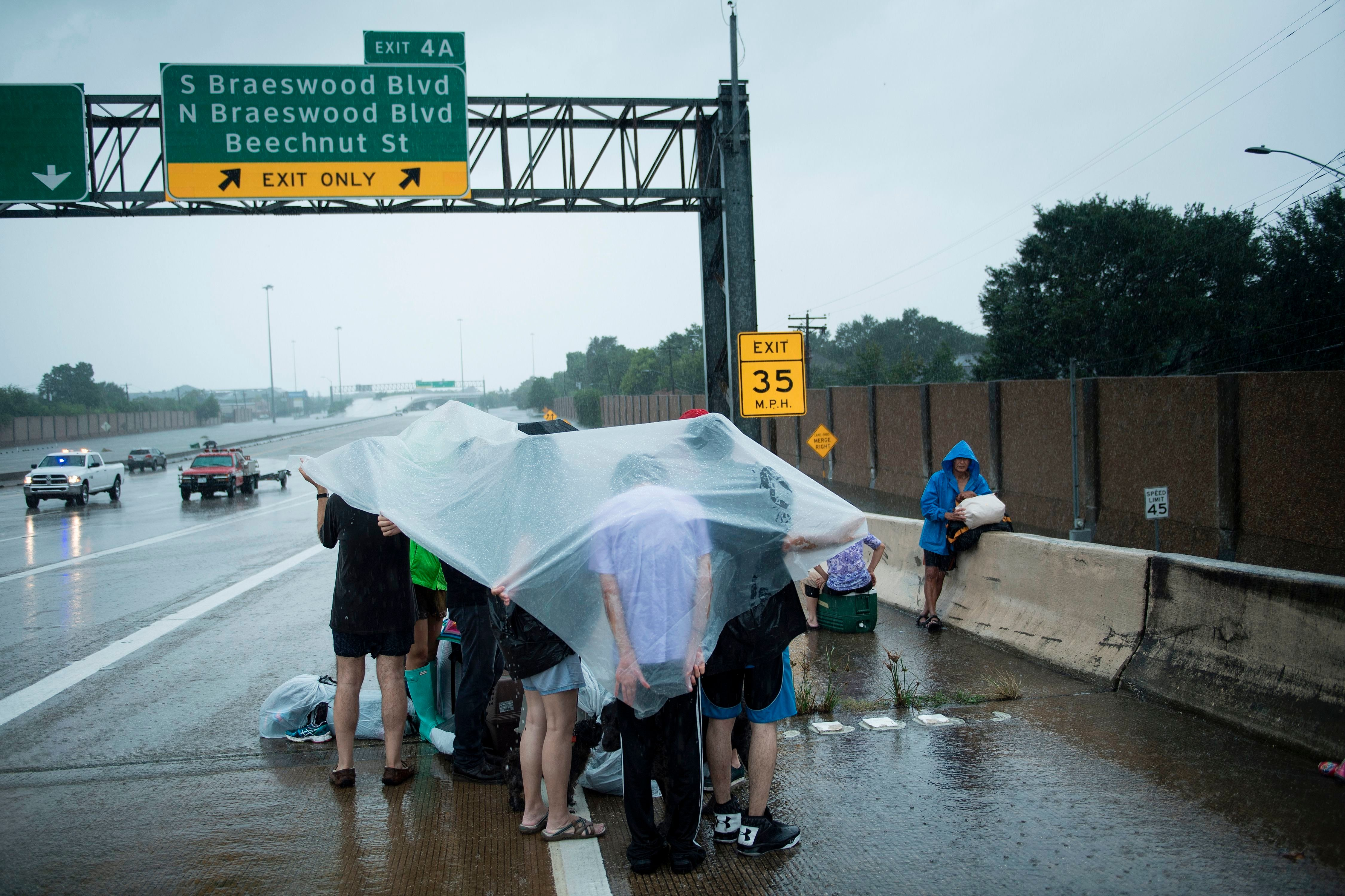 TOPSHOT - Evacuation residents from the Meyerland wait on an I-610 overpass for further help during the aftermath of Hurricane Harvey August 27, 2017 in Houston, Texas. Hurricane Harvey left a trail of devastation Saturday after the most powerful storm to hit the US mainland in over a decade slammed into Texas, destroying homes, severing power supplies and forcing tens of thousands of residents to flee. / AFP PHOTO / Brendan Smialowski        (Photo credit should read BRENDAN SMIALOWSKI/AFP/Getty Images)
