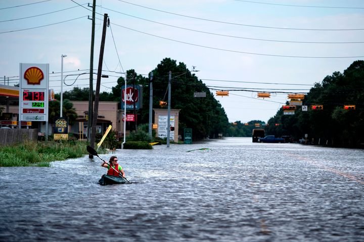 A woman paddles down a flooded road while shuttling deliveries for her neighbors during the aftermath of Hurricane Harvey on