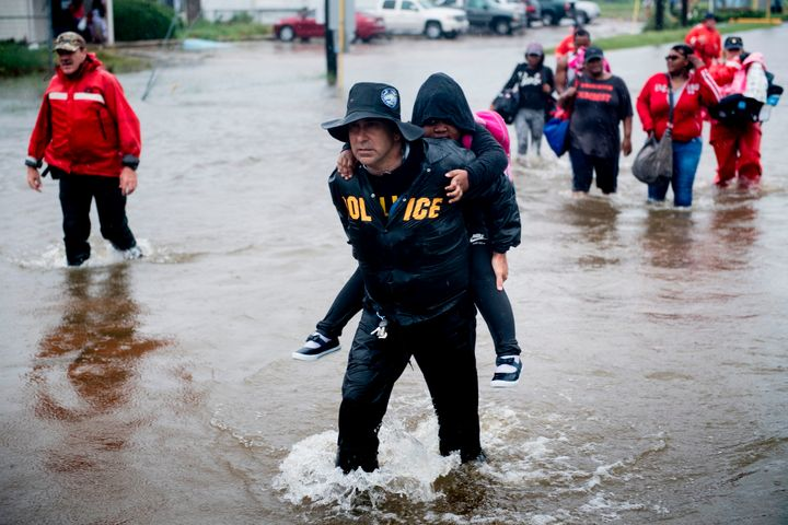 People walk to a Harris County Sheriff air boat while escaping a flooded neighborhood during the aftermath of Hurricane Harve