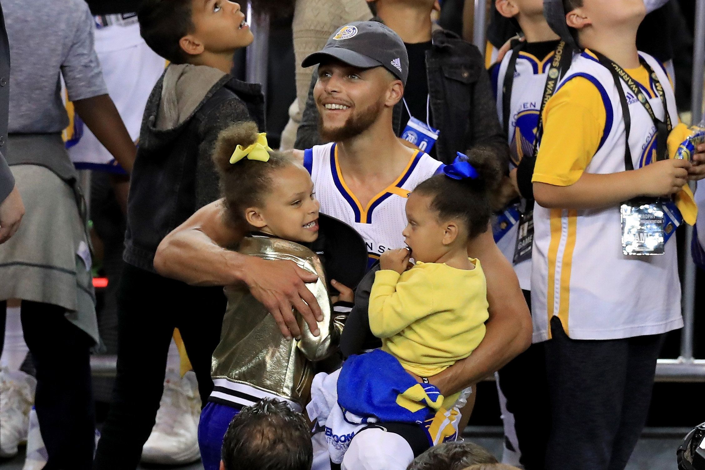 OAKLAND, CA - JUNE 12:  Stephen Curry #30 of the Golden State Warriors celebrates holding his daughters Riley and Ryan after defeating the Cleveland Cavaliers 129-120 in Game 5 to win the 2017 NBA Finals at ORACLE Arena on June 12, 2017 in Oakland, California. NOTE TO USER: User expressly acknowledges and agrees that, by downloading and or using this photograph, User is consenting to the terms and conditions of the Getty Images License Agreement.  (Photo by Ronald Martinez/Getty Images)
