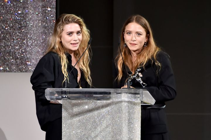 Ashley and Mary-Kate Olsen accept an award from theCouncil of Fashion Designers of America in 2018.