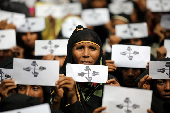 Rohingya refugee women hold placards as they take part in a protest at the Kutupalong refugee camp.