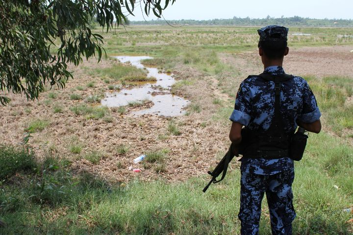 A Myanmar border guard stands guard near the Taung Pyo Letwe reception camp overlooking the border with Bangladesh, in the Ra