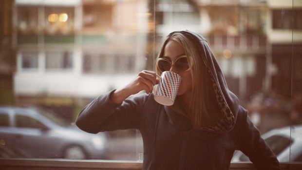 Young woman drinking late morning coffee.