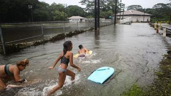HILO, HI - AUGUST 25:  Residents play in floodwaters at a baseball field during flooding from Tropical Storm Lane on the Big Island on August 25, 2018 in Hilo, Hawaii. The three day rainfall total of 31.85 inches at Hilo International Airport during the former hurricane set a new record for Hilo.  (Photo by Mario Tama/Getty Images)