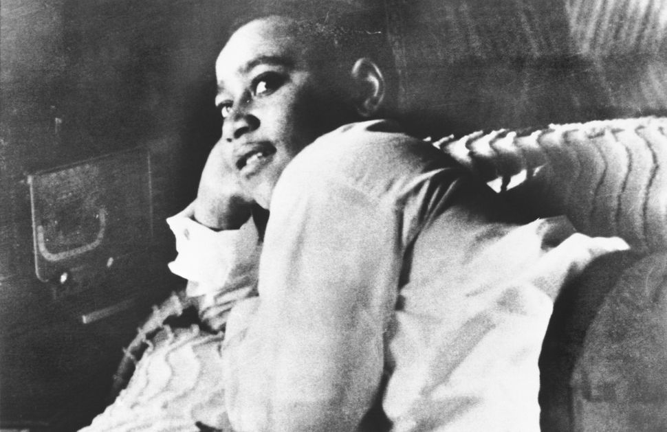 Emmett Till is photographed lying on his bed.