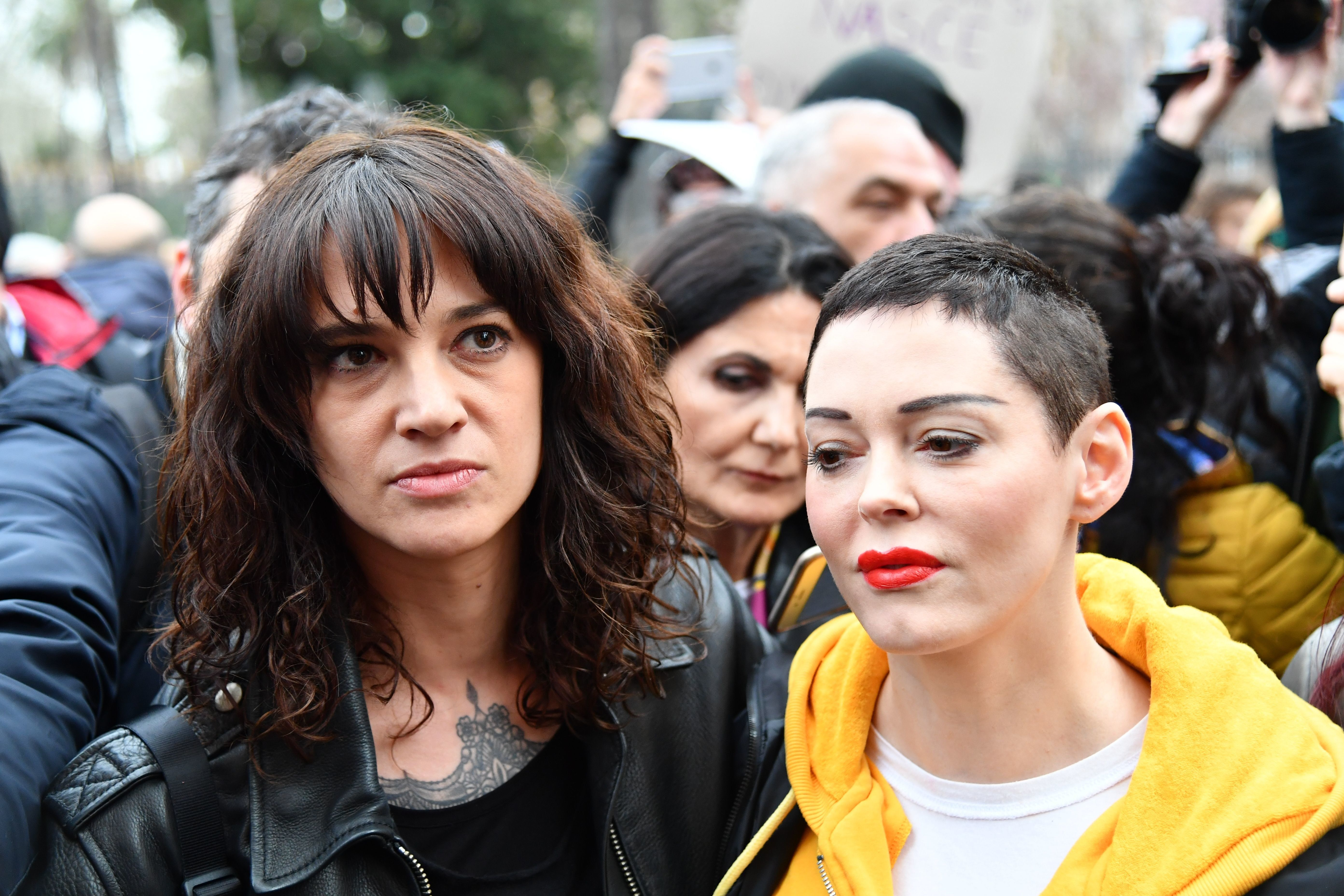 TOPSHOT - Italian actress Asia Argento (L) and US singer and actress Rose McGowan, who both accuse Harvey Weinstein of sexual assault, take part in a march organised by 'Non Una Di Meno' (Me too) movement on March 8, 2018 as part of the International Women's Day in Rome. - 'Non Una Di Meno', which translates as Not One (Woman) Less, is the equivalent of the movement that grew out of the Harvey Weinstein-spurred sexual harassment and rape revelations. (Photo by Alberto PIZZOLI / AFP)        (Photo credit should read ALBERTO PIZZOLI/AFP/Getty Images)