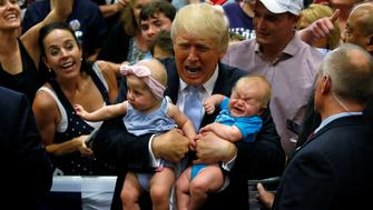 Republican presidential nominee Donald Trump holds babies at a campaign rally in Colorado Springs, Colorado, U.S., July 29, 2016. REUTERS/Carlo Allegri    TPX IMAGES OF THE DAY