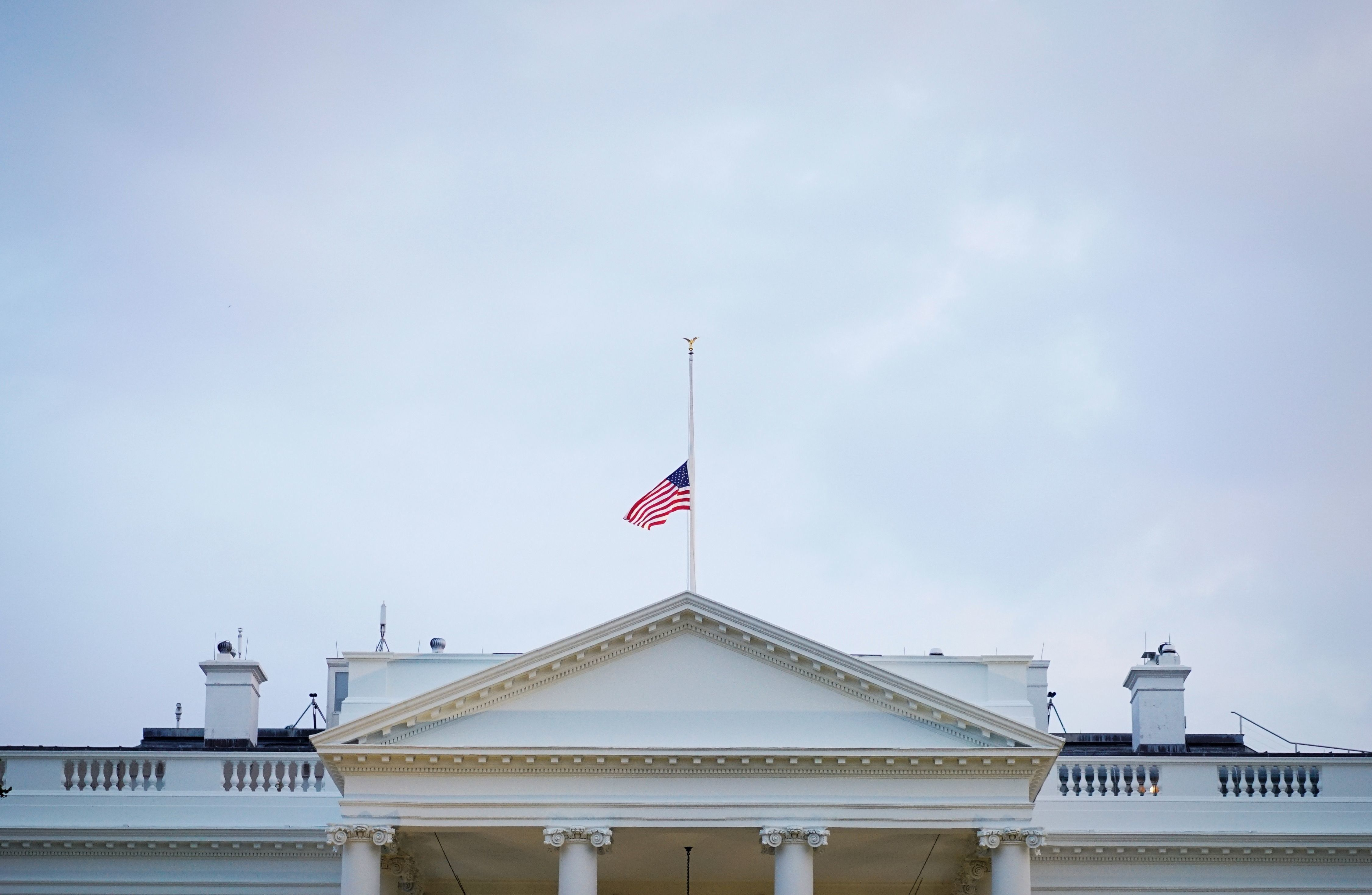 TOPSHOT - The US flag above the White House flies at half-staff in the evening in Washington, DC, on August 27, 2018. - Under fire for what critics said was a lack of respect for the late US senator John McCain, President Donald Trump issued a formal proclamation about the lawmaker's death and ordered the White House flag back to half-staff. The proclamation affects the flag atop the White House and all public buildings, as well as military installations and embassies. (Photo by MANDEL NGAN / AFP)        (Photo credit should read MANDEL NGAN/AFP/Getty Images)