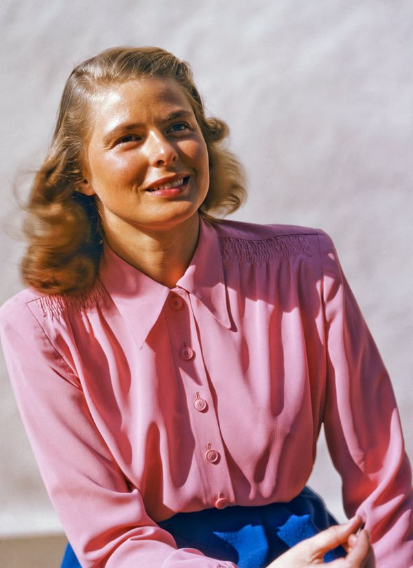 Bergman posing for a portrait in a pink blouse.